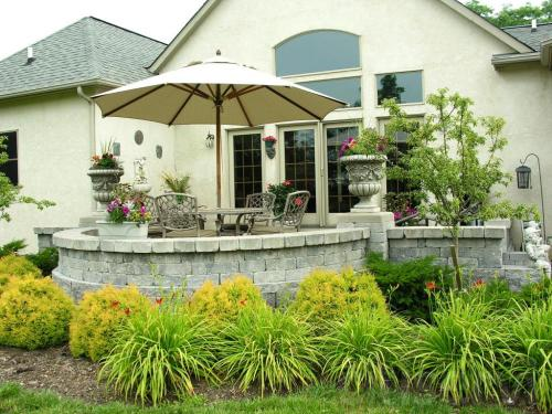 Raised patio landscape with surrounding plantings.